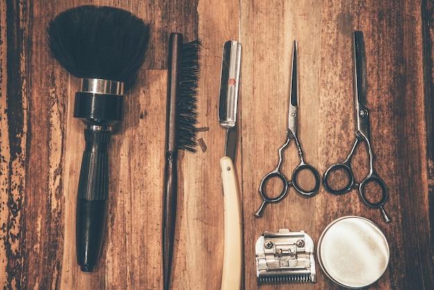 Narzędzia fryzjerskie. widok z góry narzędzi fryzjerskich leżących na słojach drewna