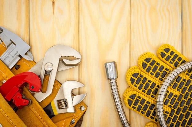 Narzędzia hydrauliczne w torbie i wężu na drewnianych deskach służą do wymiany lub naprawy