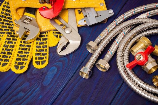 Narzędzia hydrauliczne w żółtej torbie i części zamienne na niebieskich drewnianych deskach służą do wymiany lub naprawy