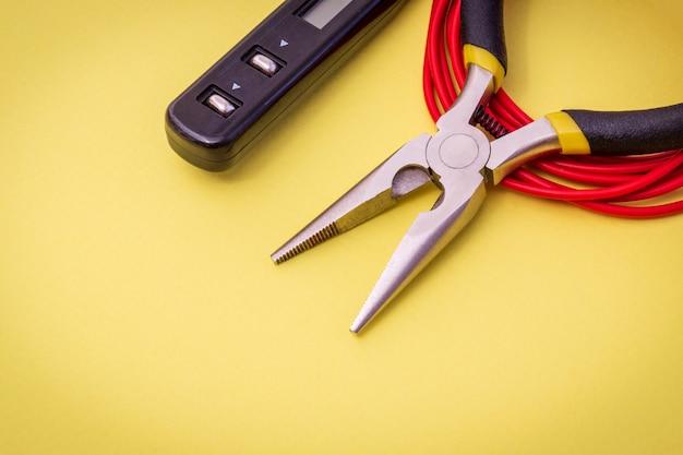 Narzędzia i drut dla elektryka na żółtej przestrzeni do naprawy systemów pod napięciem lub komunikacji