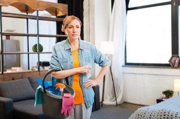 Narzędzia i produkty. rozważna jasnowłosa kobieta planująca sesję sprzątania obserwując przestrzeń