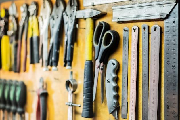Narzędzia i urządzenia wiszące na ścianie warsztatu. linijki, noże tnące, nożyczki i inne przedmioty dobrze ułożone w miejscu pracy.