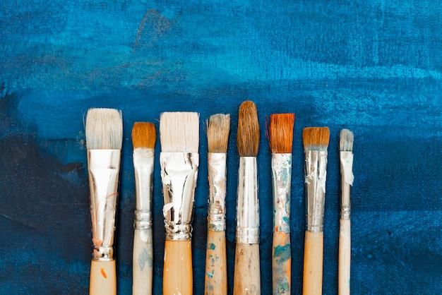 Narzędzia i wyposażenie dla artysty. paleta i pędzle z bliska. proces rysowania i kreatywności. obraz jest w kolorze niebieskim.