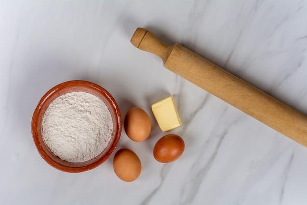 Narzędzia kuchenne, jajka, mąka i masło.