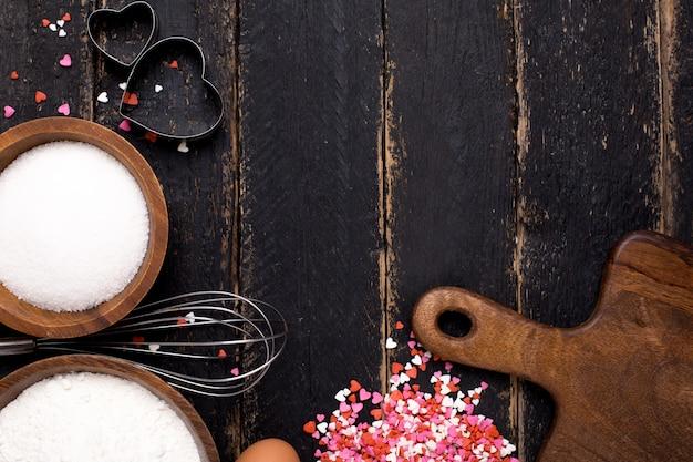 Narzędzia kuchenne, mąka, serca i cukier na drewnie