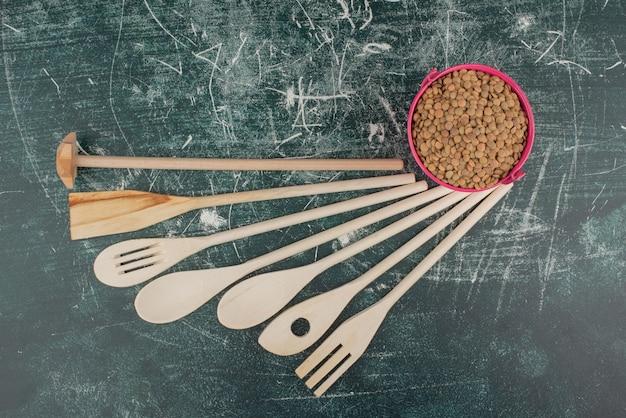 Narzędzia kuchenne z różowym wiadrem orzechów na tle marmuru. wysokiej jakości zdjęcie