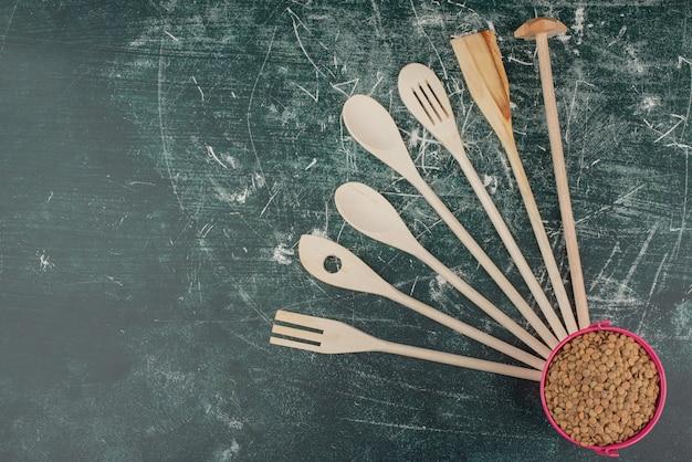 Narzędzia kuchenne z różowym wiadrem pszenicy na tle marmuru.