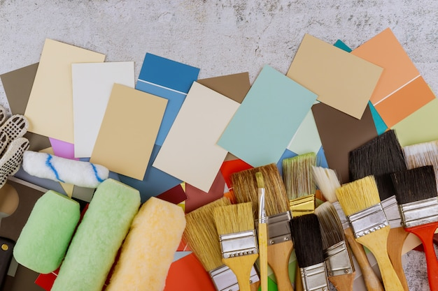 Narzędzia malarskie różne pędzle, wałek i wybór palety kolorów na drewnianym stole