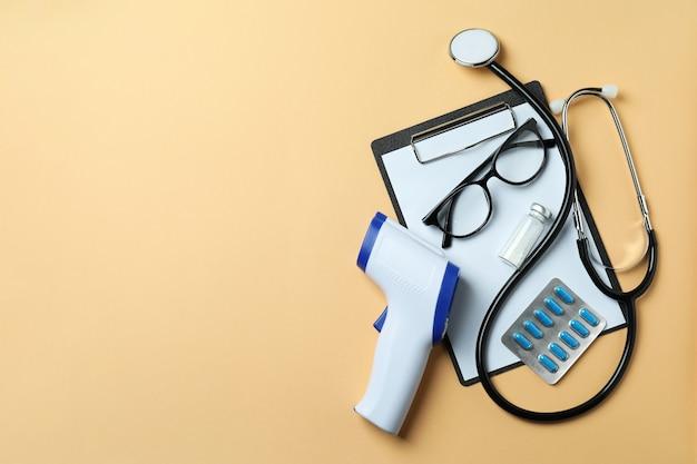 Narzędzia medyczne i pistolet termometr na beż