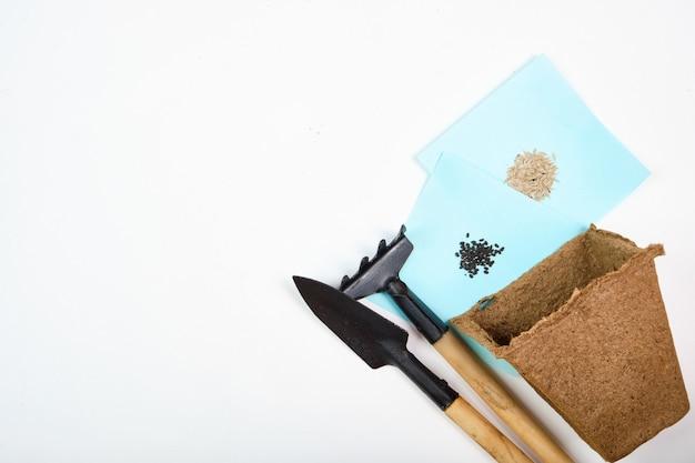 Narzędzia, nasiona, doniczki torfowe i tłoczony grunt pod sadzonki. copyspace dla tekstu, widok z góry. uprawa żywności na parapecie. flatlay na białej drewnianej przestrzeni