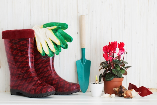 Narzędzia ogrodnicze i gumowe buty na białym drewnianym stole