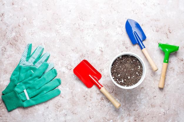 Narzędzia ogrodnicze na lekkim stole z rośliną domową i rękawiczkami
