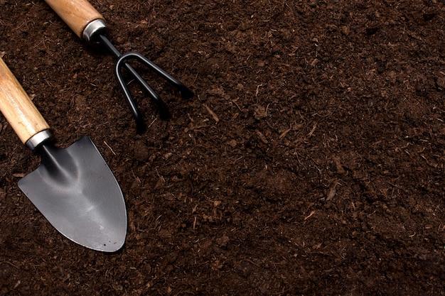 Narzędzia ogrodnicze na tle gleby. koncepcja ogród wiosna. układ poziomy z wolnym miejscem na tekst przechwycony z góry, widok z góry, flatlay,