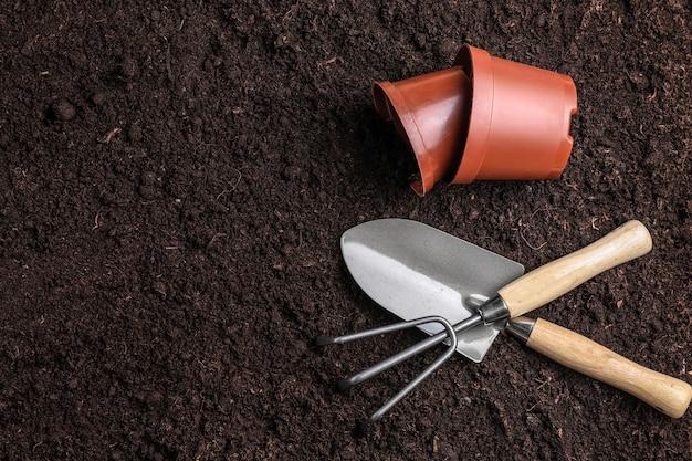 Narzędzia ogrodnicze z doniczkami na ziemi