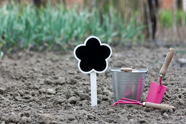 Narzędzia ogrodnicze ze znakiem, wiadrem, grabiami i łopatą w ogrodzie