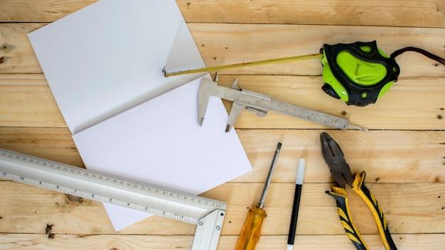 Narzędzia pomiarowe z białym papierze na drewnianym stole