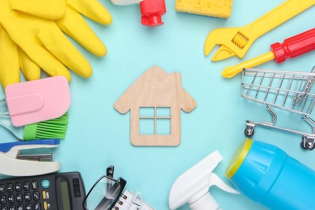 Narzędzia pracy, środki czystości i artykuły papiernicze z domem w środku na niebiesko.