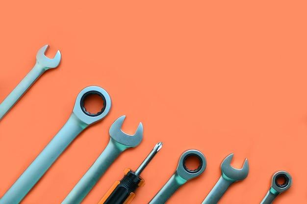 Narzędzia: śrubokręt, klucz na pomarańczowym tle