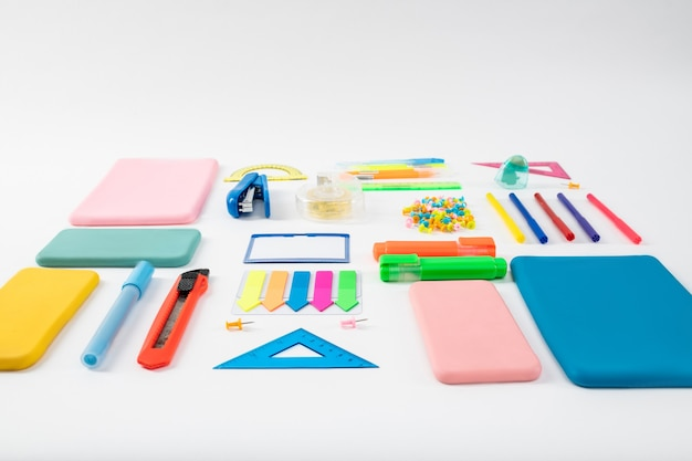 Narzędzia stacjonarne. bukiet kolorowych jasnych pudełek stacjonarnych i gadżetów leżących na białej powierzchni w oświetleniu studyjnym