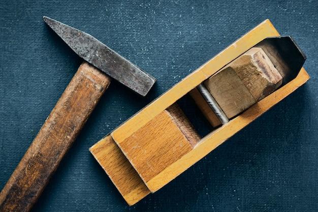 Narzędzia stolarskie, stary młotek i strugarka ręczna na niebieskim stole