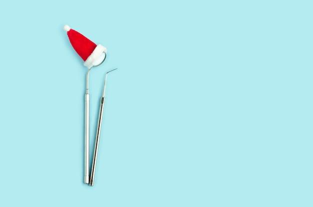 Narzędzia stomatologiczne na nowy rok, lusterko i sonda w czapce mikołaja, leżanka płaska
