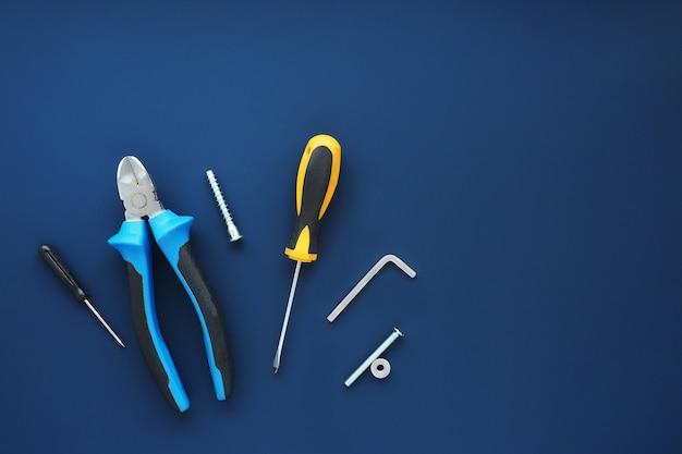 Narzędzia szczypce, śrubokręty, klucze, śruby, wkręty samogwintujące, nakrętka na ciemnym niebieskim tle. miejsce na tekst.