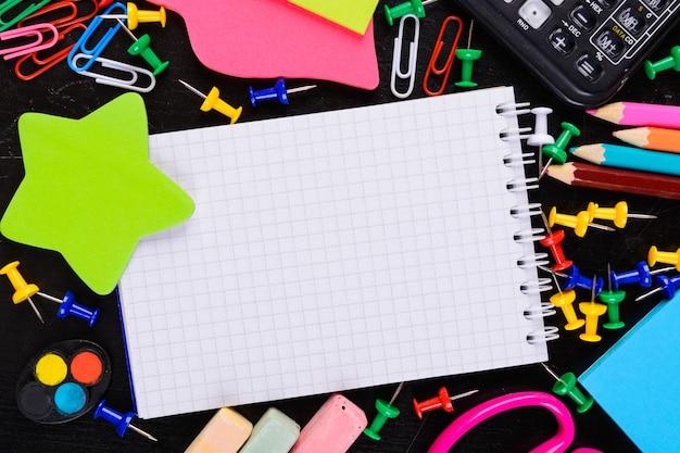Narzędzia szkolne z pustym notatnikiem w centrum z kopią przestrzeni na czarnym tle z powrotem do szkoły