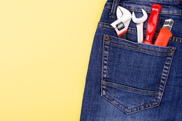 Narzędzia w kieszeni jeansów rzemieślnika na żółtej ścianie z miejscem na tekst