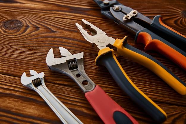 Narzędzia warsztatowe, drewniany stół. profesjonalne narzędzia, sprzęt stolarski lub budowlany, klucze i pale