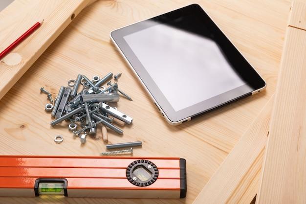 Narzędzie budowlane i cyfrowa tabletka leżą na lekkim drewnianym stole