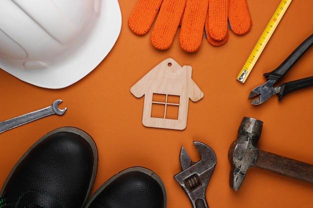 Narzędzie do majsterkowania. narzędzia budowlane i postać domu na brązowym tle. kompozycja płaska świecka. widok z góry
