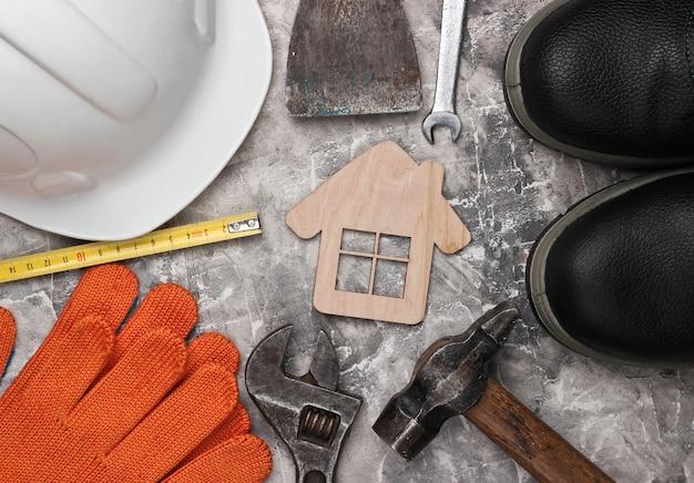 Narzędzie do majsterkowania. narzędzia budowlane i postać domu na szarym tle betonu. kompozycja płaska świecka. widok z góry