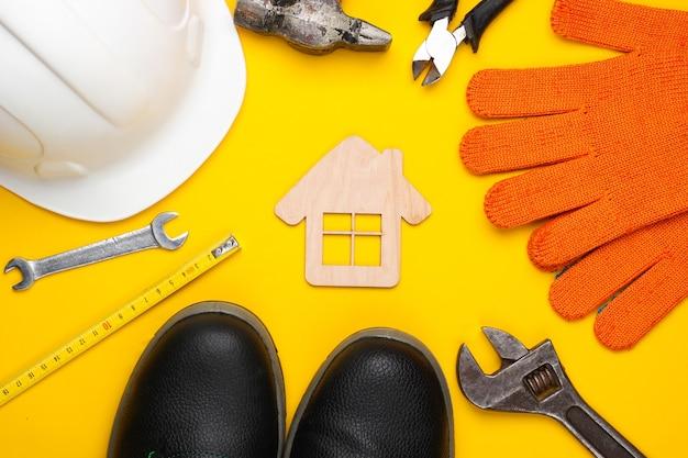 Narzędzie do majsterkowania. narzędzia budowlane i postać domu na żółtym tle. kompozycja płaska świecka. widok z góry