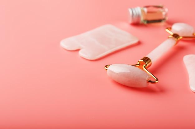 Narzędzie do masażu gua sha wykonane z naturalnego różowego wałka kwarcowego, jadeitu i oleju, na różowym tle do pielęgnacji twarzy i ciała. część tradycyjnej medycyny chińskiej