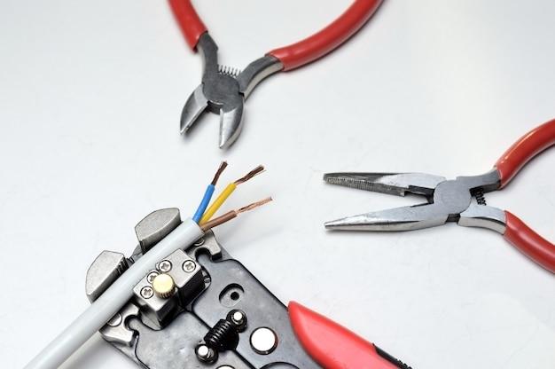 Narzędzie do ściągania izolacji, ekranowany drut trójżyłowy i przecinaki do drutu na białym tle. zbliżenie