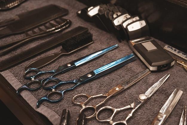 Narzędzie fryzjerskie w zakładzie fryzjerskim. narzędzie fryzjerskie. nożyczki, grzebienie, maszynki do golenia, maszynki do strzyżenia. narzędzie dla kreatora. organizacja miejsca pracy. selektywne ustawianie ostrości.
