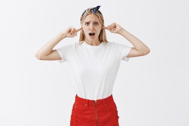 Narzekająca z niepokojem młoda blond dziewczyna pozująca pod białą ścianą