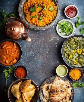 Narzut tradycyjnych indyjskich potraw i przystawek: curry z kurczaka, pilaw, chleb naan, samosy, paneer, chutney na rustykalnym tle. stół z wyborem potraw kuchni indyjskiej, miejsce na tekst