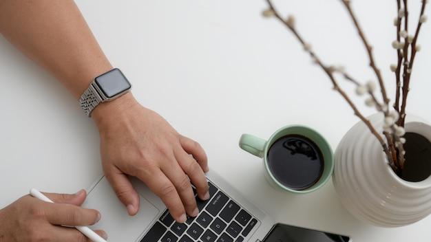 Narzutów strzał mężczyzn pisania na laptopie z rysika, filiżanki kawy i dekoracji