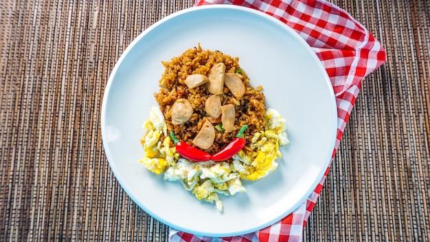 Nasi goreng (smażony ryż) z jajecznicą przyozdobioną plastrami świeżych klopsików na talerzu. gotowany na ostro w azjatyckim stylu smażony ryż.