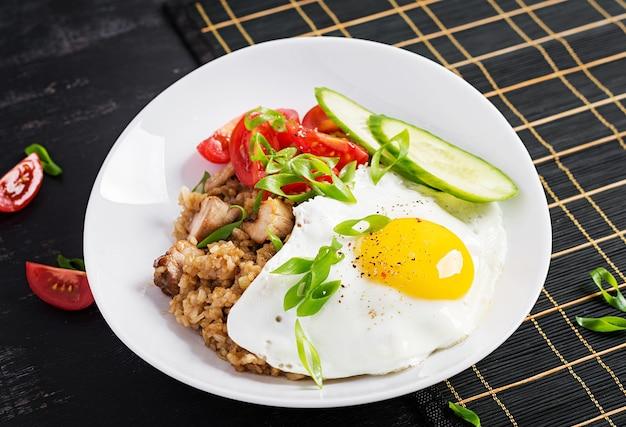 Nasi goreng. smażony ryż z kurczaka indonezyjski na ciemnym tle. nasi goreng to danie kuchni indonezyjskiej z ryżem, mięsem z kurczaka, cebulą, jajkiem, warzywami.