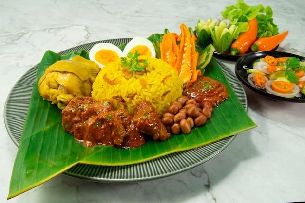 Nasi lemak ryż biryani podany z wołowiną rendang, ayam, orzeszkami ziemnymi, gotowanym jajkiem.