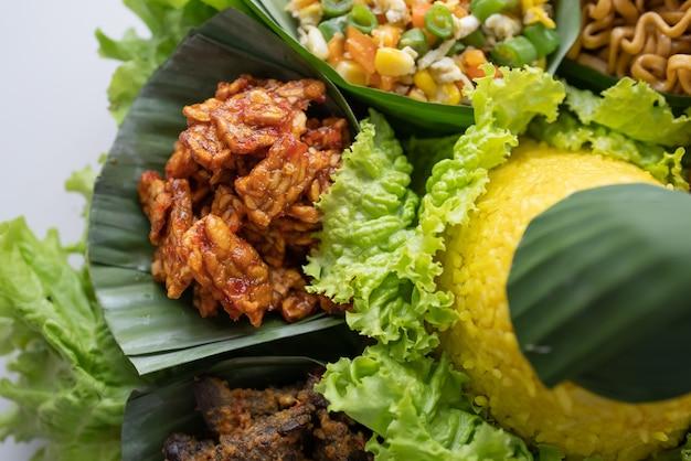 Nasi tumpeng kuchnia indonezyjska żółty ryż na liściu bananowca