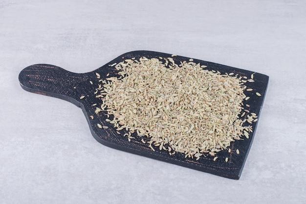 Nasiona anyżu zielonego na drewnianej desce na betonowej powierzchni
