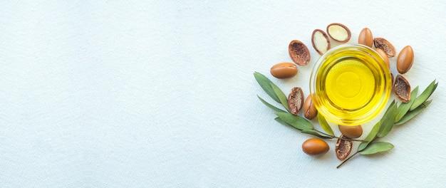 Nasiona arganowe i olej na białym tle na tle białego transparentu