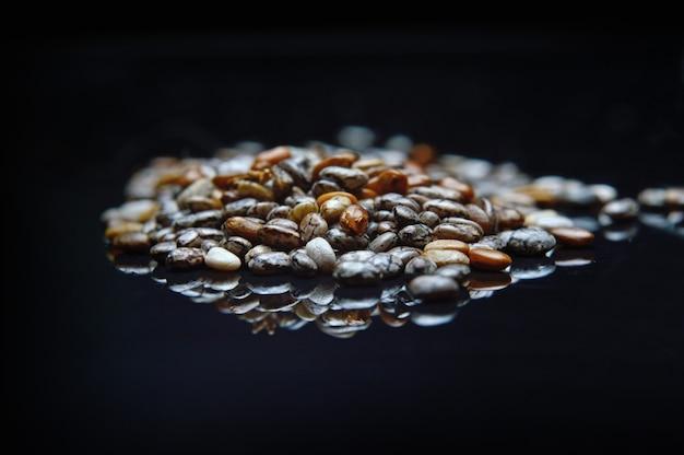 Nasiona chia na czarnej błyszczącej powierzchni z bliska.