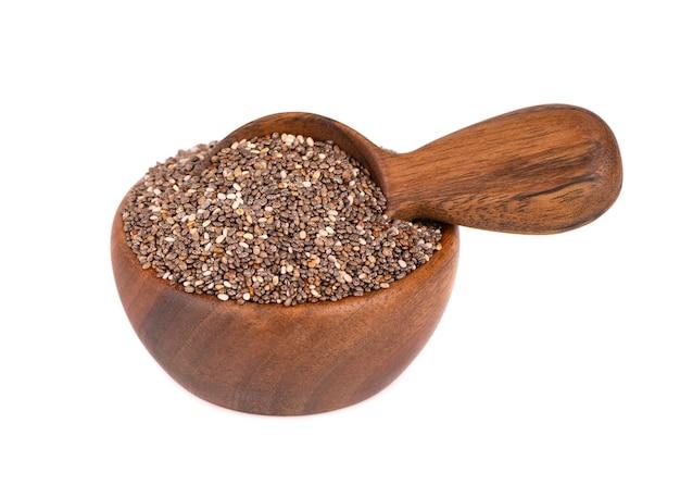 Nasiona chia w drewnianej misce i łyżką, na białym tle.