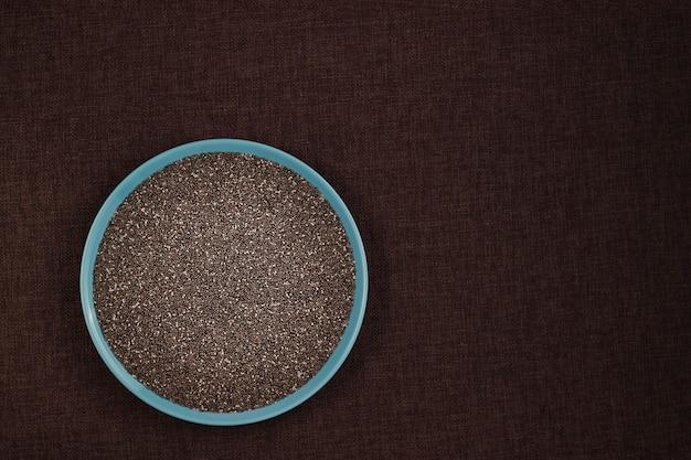 Nasiona chia w niebieskim talerzu na lnianym obrusie z miejscem na kopię przepisu