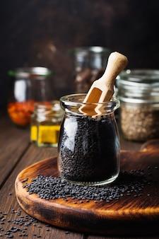 Nasiona czarnego sezamu w małym szklanym słoju na ciemnym tle. selektywne skupienie.