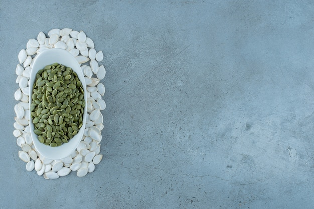 Nasiona dyni na białym tle na niebieskim tle. zdjęcie wysokiej jakości